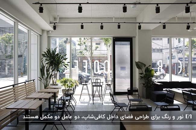 طراحی کافی شاپ سفید با میز و صندلی های چوبی روشن و پایه های مشکی و چراغ های سقفی مشکی
