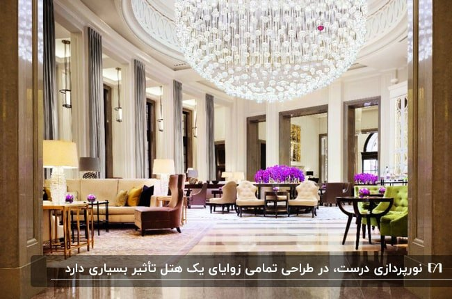طراحی داخلی لابی هتل با صندلی های رنگی، گلهای بنفش و لوستر گرد کریستالی