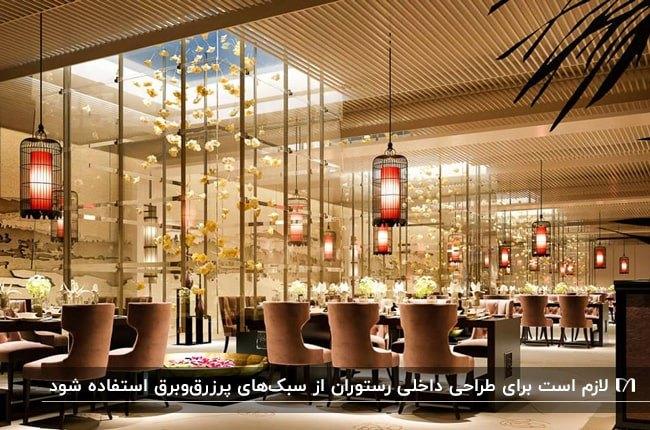 رستورانی مدرن با میزو صندلی هایی با تناژ قهوه ای و چراغ های آویز مشکی و قرمز