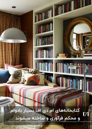 تصویر اتاقی با قفسه های کتاب ام دی اف سفید و یک مبل ال شکل با پارچه راه راه رنگی و آباژور