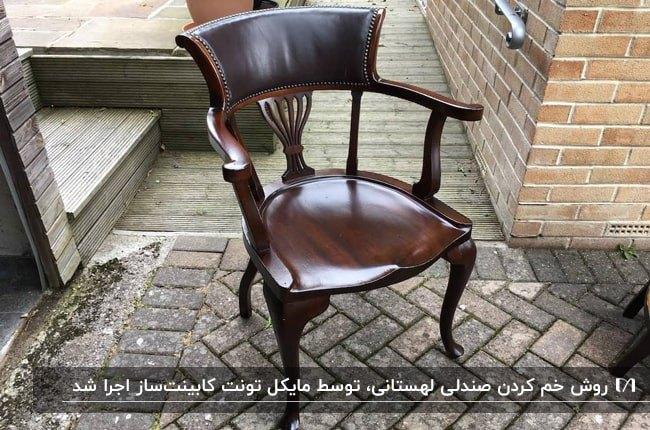 تصویر یک صندلی لهستانی قهوه ای تیره براق در فضای بیرونی