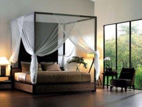 تخت خواب قهوه ای پرده داری با پرده های سفید و دو آباژور اطرافش مقابل دیوار شیشه ای