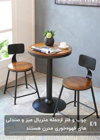 تصویر دو صندلی و میز گرد چوبی و فلزی مشکی