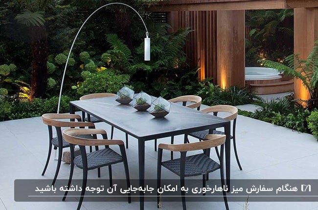 میز ناهارخوری مدرن چوبی و مشکی به همراه آباژور پایه بلند در تراس گاردن