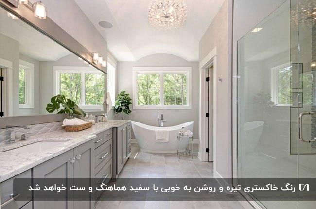 سرویس بهداشتی بزرگی با ترکیب رنگ طوسی و سفید، لوستر آویز و آینه بزرگ مستطیلی