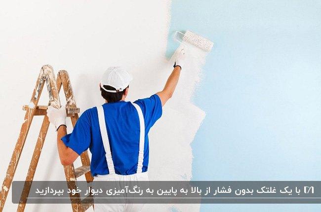تصویر مردی روی نردبان چوبی در حال سفید کردن از بالا به پایین دیوار آبی