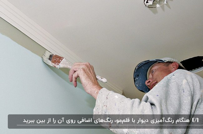 مردی در حال رنگ آمیزی لبه های بالای دیوار با قلم مو