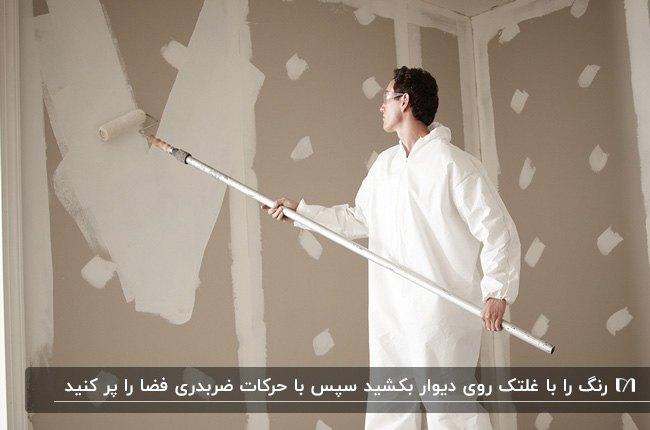 مردی با لباس فرم سفید در حال زدن رنگ سفید روی دیوار کرم با غلتک بلند