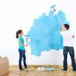 تصویر یک مرد و یک زن در حال رنگ آمیزی آبی دیوار سفید اتاقی با کفپوش چوبی