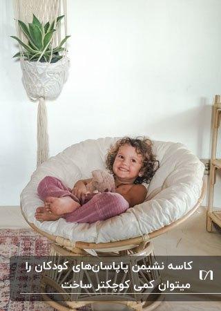 تصویر یک مبل پاپاسان چوبی مخصوص کودکان کنار گلدان سفید آویز