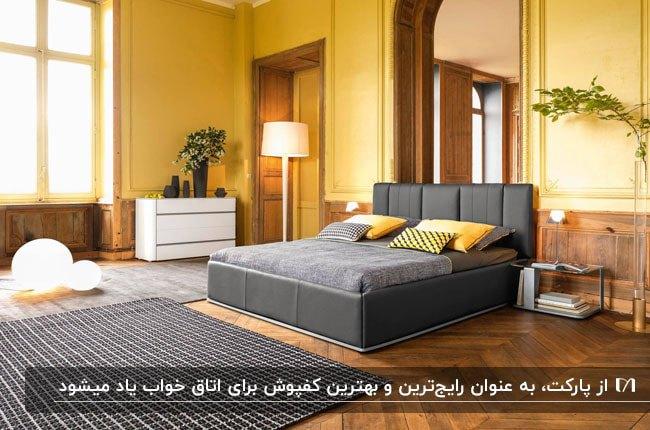 اتاق خوابی با دیوارهای زرد رنگ، مبل و فرش خاکستری و کفپوش پارکت