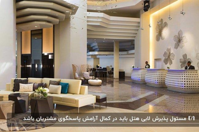 لابی هتلی با سه میز رسپشن سفید طرحدار کنار هم و سقف طبقه ای گچکاری شده