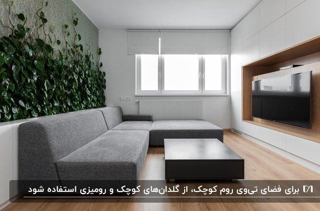 اتاق تلویزیون با مبل ال شکل طوسی، دیواری با گیاهان پیچکی و دیوار چوبی