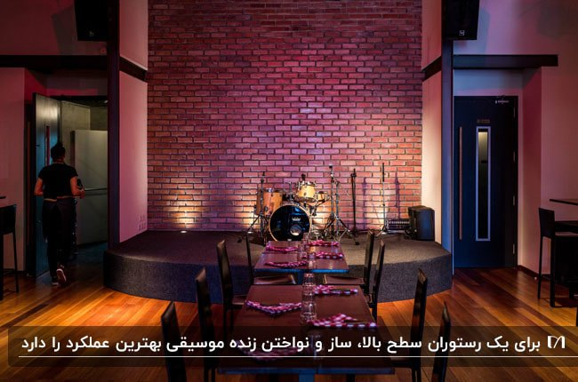 رستورانی با میز چوبی و صندلی های مشکی مقابل محل برگذاری موسیقی زنده با دیوار آجری