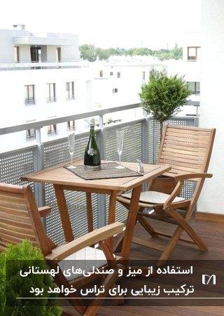 تصویر یک تراس با حفاظ سفید رنگ و میز و دو صندلی لهستانی چوبی تاشو