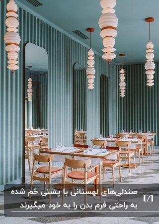 رستورانی با دیوارها و سقف سبز رنگ، میز وصندلی های لهستانی با پارچه نارنجی و لوستر های آویز