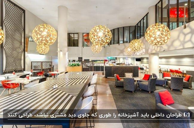 فضای داخلی رستوران بزرگی با مبلمان خاکستری با کوسن های قرمز