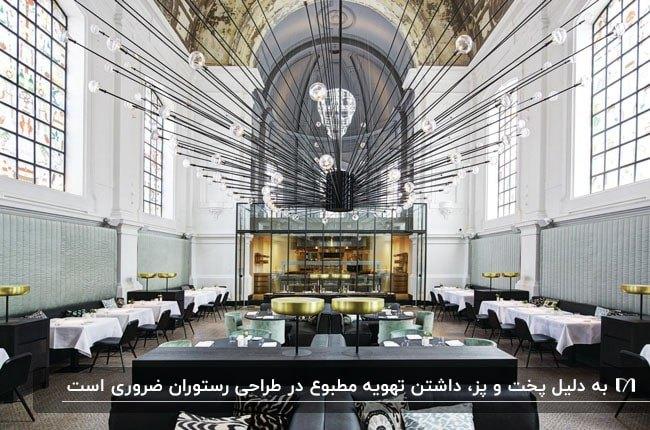 رستوران بزرگی با سقف نیم دایره بلند و میز وصندلی های سفید و مشکی و پنجره های بزرگ