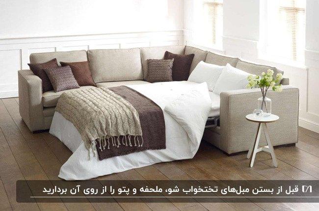 مبلمان ال شکل تخت شو به رنگ کرم با کوسن های کرم و قهوه ای و دو شال مبل