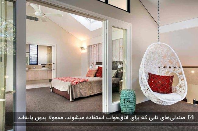 اتاق خواب بزرگی با کفپوش خاکستری، تخت دو نفره و صندلی تابی بدون پایه سفید با کوسن قرمز