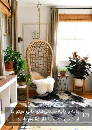 تصویر اتاقی با کفپوش، گلدان ها، پایه گلدان ها و صندلی تابی بدون پایه چوبی