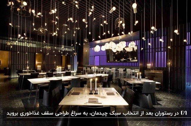 رستورانی با تم رنگی مشکی و میزهای چوبی با چراغ های آویز سقفی