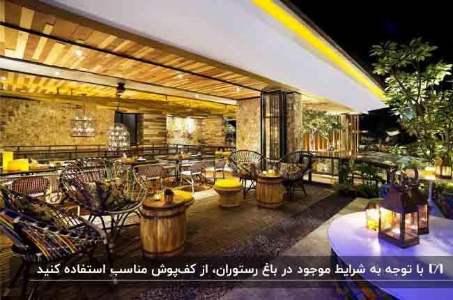 تصویر باغ رستورانی با کفپوش و سقف چوبی به همراه نورپردازی های زرد رنگ