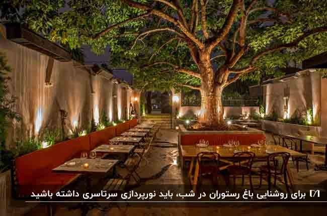 باغ رستورانی با نیمکت های قرمز، صندلی ها و میزهای چوبی و نورپردازی های نقطه ای