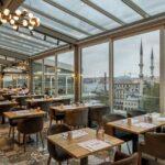 رستورانی با میزهای مربع چوبی و صندلی های خاکستری با دیوار و سقف شیشه ای