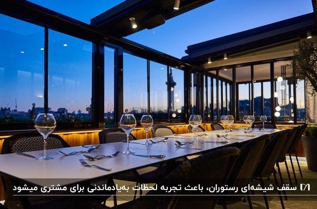 رستورانی با دیوار و سقف شیشه ای با فریم فلزی مشکی