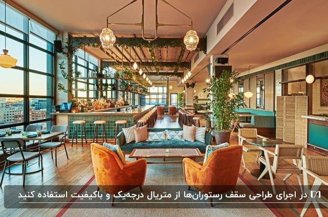 رستورانی مدرن با مبلمان و میز و صندلی های آبی و نارنجی و سقف گچ با گیاهان رونده