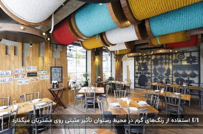 رستورانی با میزهای غذاخوری چوبی و صندلی های فلزی با طراحی سقف توسط نخ های قرقره رنگی