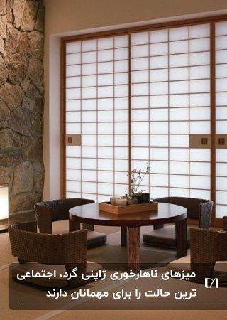 میز ناهارخوری گرد ژاپنی با چهار صندلی به رنگ قهوه ای تیره کنار درب مشبک