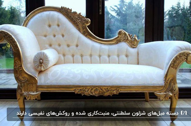 تصویر مبل شزلون سلطنتی با فریم سلطنتی طلایی و پارچه کرم رنگ روشن جلوی دیوار شیشه ای