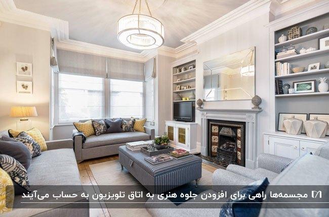 اتاق تلویزیون با دیوار های سفید، قفسه های دیواری و مبل های طوسی رنگ