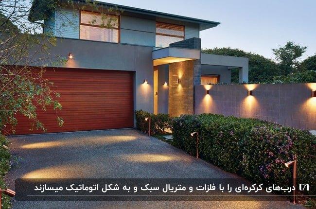 ویلایی با نمای طوسی و خاکستری و درب ورودی کرکره ای آجری با نورپردازی های دیواری