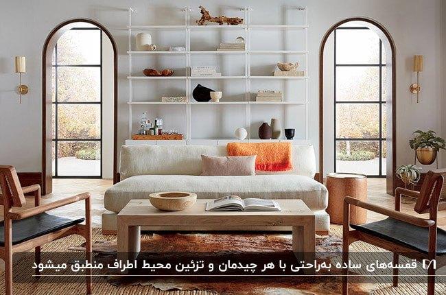 نشیمنی مدرن با مبل سفید و دو صندلی تک نفره چوبی به همراه قفسه های سفید دیواری