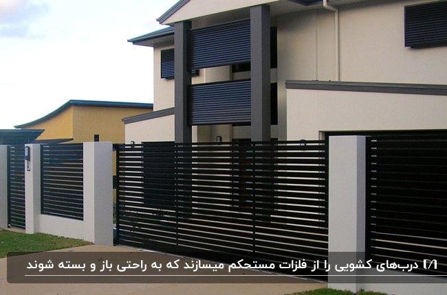خانه دو طبقه ای با نمای سفید و طوسی و سرمه ای و درب ورودی کشویی مشکی