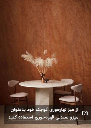 میز غذاخوری گرد سنگی با صندلی های سفید بعنوان میز قهوه خوری