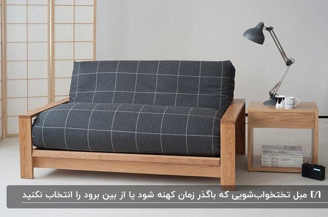 کاناپه تخت خواب شو با فریم چوبی و پارچه مشکی با خط های سفید کنار میز عسلی چوبی