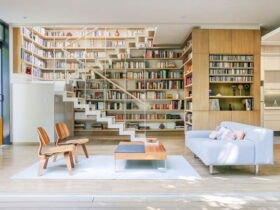 نشیمنی با دیوارپوش چوبی و کتابخانه بزرگی زیر راه پله طبقه دوم