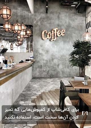 طراحی کافی شاپ با دیوارهای خاکستری، میز و صندلی های چوبی و کفپوش ترکیبی چوب