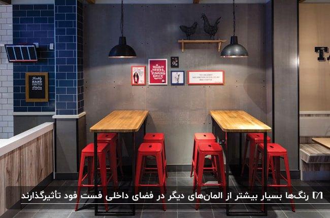 فست فودی با دیوارهای خاکستری، میزهای چوبی و چهارپایه های قرمز