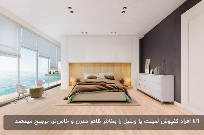 اتاق خواب مدرنی با یک دیوار خاکستری، یک دیوار شیشه ای، تخت دو نفره چوبی و کفپوش چوبی روشن