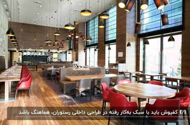 طراحی داخلی رستورانی با میزهای چوبی و صندلی های قرمز و قهوه ای، کفپوش چوبی و چراغ های آویز
