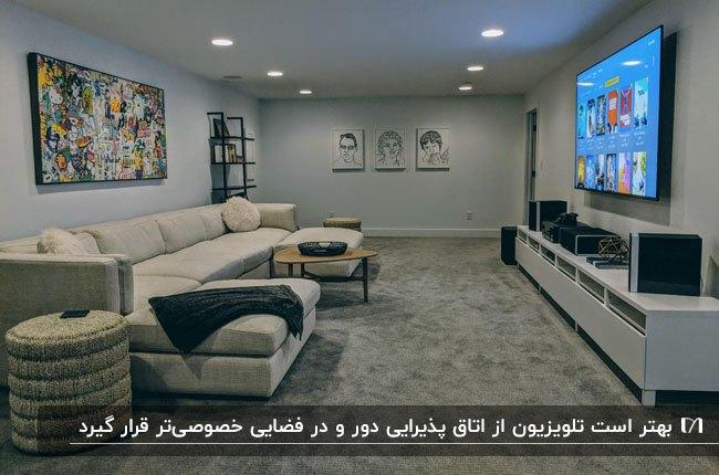 اتاق تلویزیون با دیوارهای طوسی، مبل ال شکل کرم . تابلوهای نقاشی دیواری