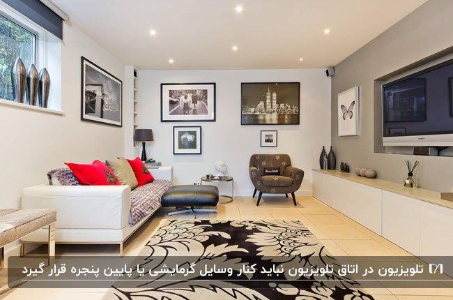 اتاق تلویزیون با دیوار خاکستری، مبل سفید و کوسن های قرمز با قاب های عکس روی دیوار