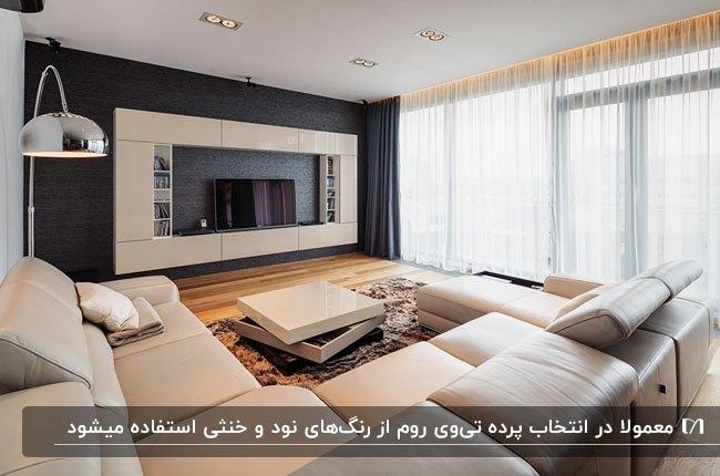 اتاق تلویزیونی با مبلمان چرم کرم رنگ، کفپوش چوبی و پرده های حریر سفید