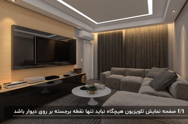 اتاق تلویزیون با مبل ال شکل کرم، دیوار پشت تلویزیون گلبهی و پرده قهوه ای
