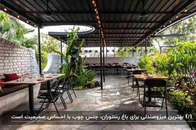 تصویر باغ رستورانی با میزهای چوبی و صندلی های مشکی و کفپوش سنگی